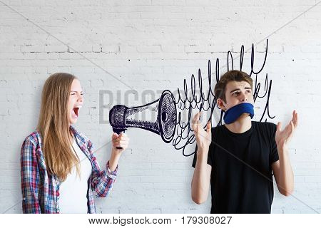 Freedom of speech concept. Young woman screaming into drawn megaphone with guy having no right to speak on white brick background