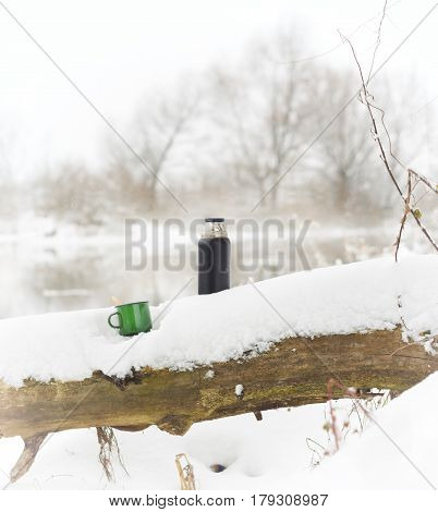 Cup with a hot drink and a thermos. Winter shore of the river in the fog