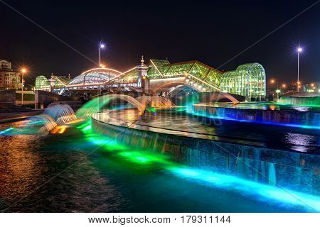 MOSCOW - AUGUST 20, 2013: Bogdan Khmelnitsky bridge and fountain at night in Moscow. It is a beautiful pedestrian bridge across the Moscow River near Kievsky railway station.