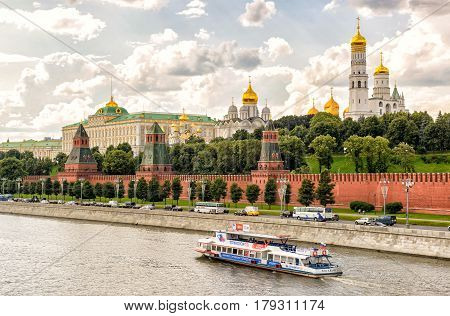 MOSCOW - JULY 10, 2015: Tourist boat floats on the Moscow River near the Kremlin. The Kremlin is the main attraction of Moscow.