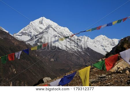Snow capped mountain and prayer flags. Spring scene near Namche Bazar Everest National Park.