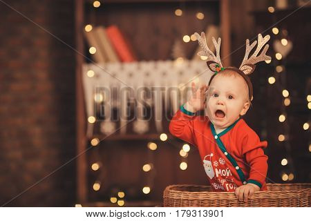 Little Baby Boy In Reindeer Antlers Sitting In A Wicker Basket