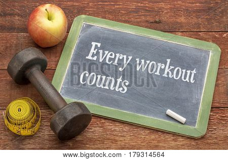 Every workout counts motivational concept -  slate blackboard sign against weathered red painted barn wood with a dumbbell, apple and tape measure