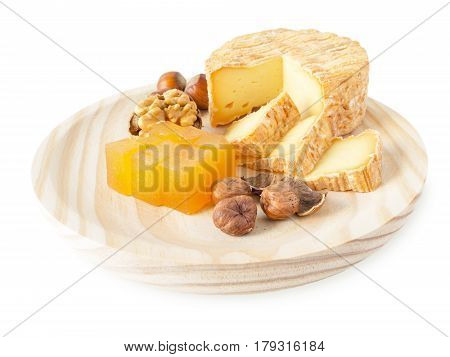 Soft washed-rind cheese hazelnuts walnut and marmalade on the textured wooden board isolated on white