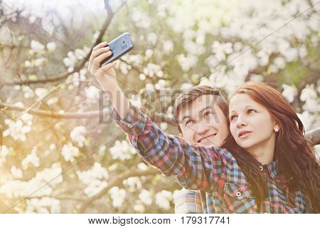 Young cheerful couple making selfie on a background of flowering tree