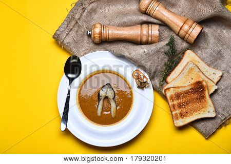 Cream Soup Brown Color With Fish, Toast, Pepperbox, Thyme, Saltcellar
