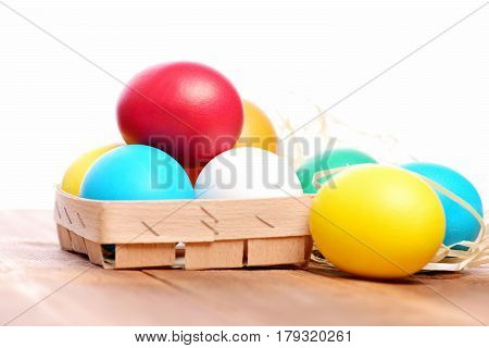 Easter Colorful Eggs In Wooden Basket With Straw Nest