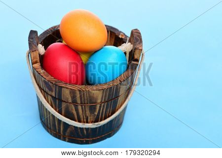 Painted Easter Colorful Eggs In Wooden Bucket On Blue Background