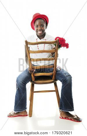 A happy preteen girl sitting backwards on a ladder-back chair while holding a bouquet of red flowers.  On a white background.