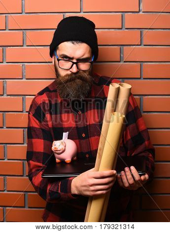 Bearded man long beard. Brutal caucasian serious unshaven hipster holding craft paper rolls piggy bank on laptop in checkered shirt with hat and glasses on brown brick wall studio background