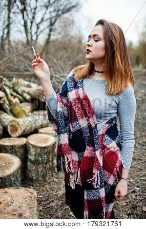 Young Girl Smoking Cigarette Outdoors Background Wooden Stumps. Concept Of Nicotine Addiction By Tee