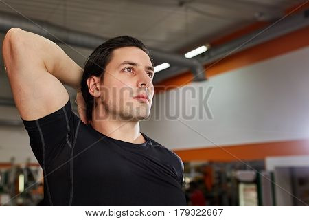 Portrait Of A Athlete Man Measuring His muscles In The Gym. Beautiful face of the sportsman. Closeup. One hand. Athlete in the sportwear, black t-shirt. Posture. Healthy lifestyle.