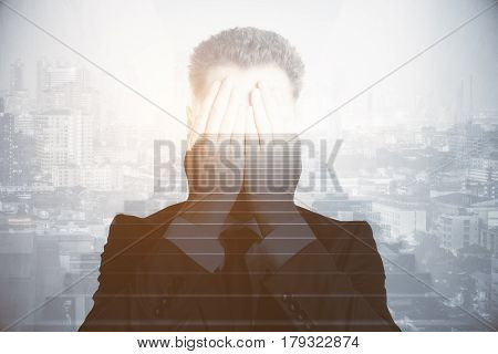 Stressed young businessman covering face with hands on abstract city background with staircase. Growth and risk concept. Double exposure