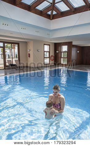 Mother playing with her baby at swimming pool indoor. Kids learn to swim during family vacation