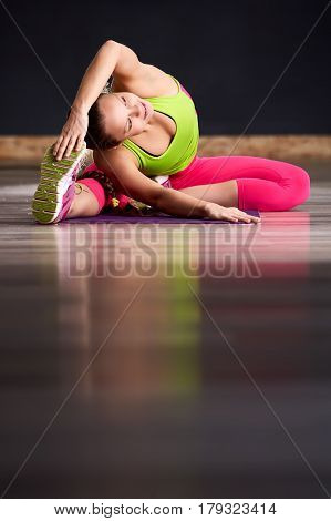 Professional woman exercising and stretching her body doing flexibility exercises and bending her back, sitting on a violet yoga mat indoors. Dark background. Woman in the colorful sportwear. Healthy lifestyle. Vertical photo.