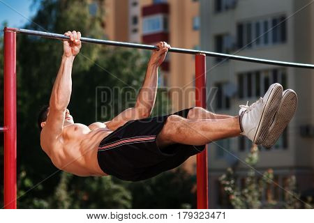 Young muscular build man doing pull ups exercises on horizontal bar outdoors, strong athletic runner in fluorescent copy space t-shirt training hard at sunny afternoon outside, sportsman working out. Face is not visible.