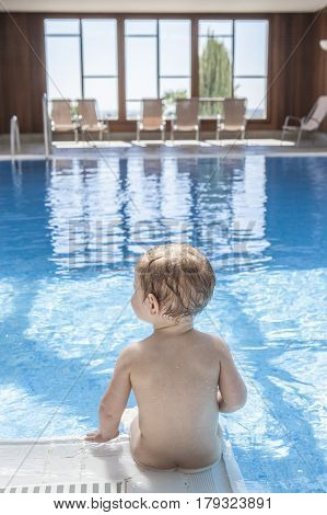 Cute little baby boy sitting at the edge of pool. He is putting his legs into the water