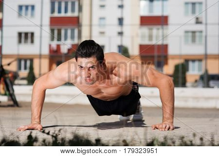 Low angle view of a fit young man doing press-ups on the outdoor as part of his daily exercise regime. Healthy life-style. Sportsmen's face, view, abs. Black short.
