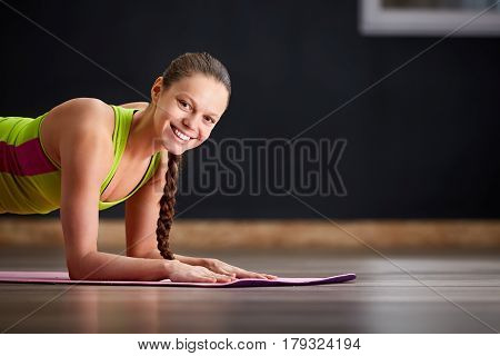 Portrait of smiling yoga woman. Yoga, fitness, sport, training and lifestyle concept - smiling woman stretching leg on mat in gym. On the pink yoga mat. Woman in sporty clothes. Healthy lifestyle.