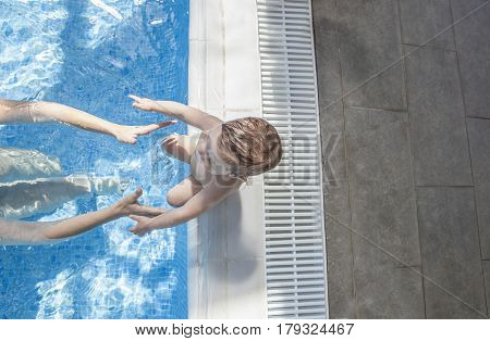 Mother playing with her baby at swimming pool indoor. He reaches hand for mother