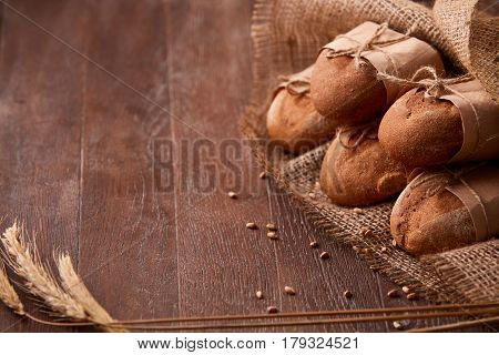 Fresh rye bread on the wooden table, wheat, paper bags, ears of wheat, rope and burlap. Brown background. Delicious food. Fresh baking. Tasty and appetizing. Angle position.