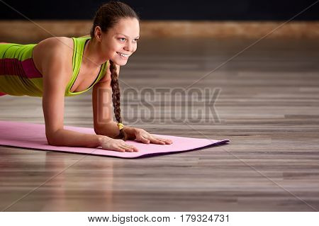 Portrait of beautiful young woman doing yoga exercise - smiling woman on the yoga mat. Sporty woman in the sporty clothes, pink leggings and green t-shirt. Healthy lifestyle.
