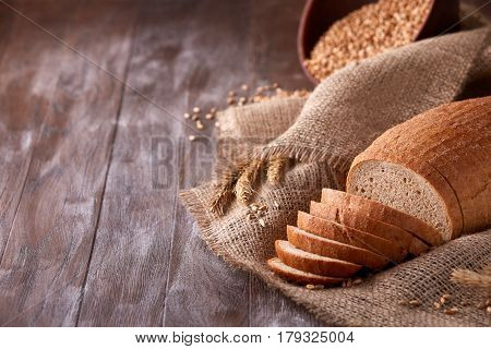 Slices of bread on burlap on the wooden table. still life composition with wheat ears scattered around and ears of wheat. Bakery and grocery food store concept.