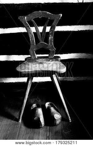 The historical clogs lying under antique chair. poster