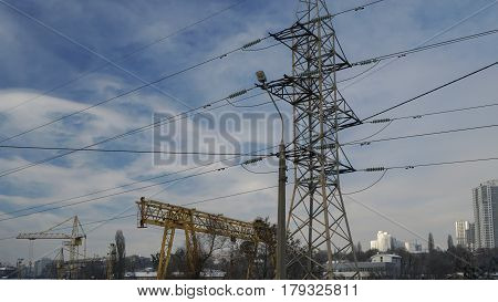 Part of the crane and electricity pylon against blue sky.