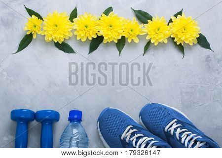 Summer spring flatlay sports composition with blue sneakers dumbbells bottle of water and yellow chrysanthemum flowers and green leaves on gray concrete background. Concept healthy lifestyle sport and diet in summer spring. Horizontal orientation top view