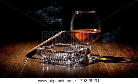 Cigar on ashtray and cognac on a wooden table