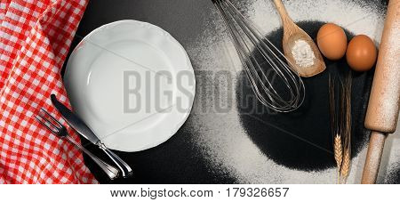 Baking background with empty plate and silver cutlery on a black table with rolling pin whisk eggs spoons ears of wheat and a checkered tablecloth
