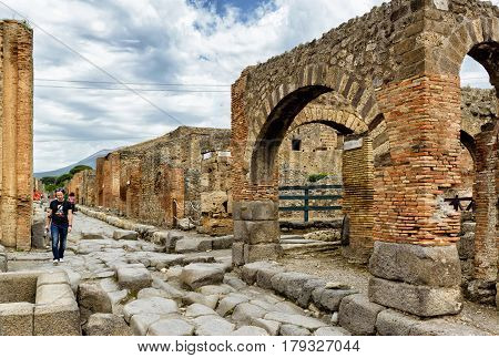 POMPEII, ITALY - MAY 13, 2014: Tourist walking in the street among the ruins. Pompeii is an ancient Roman city died from the eruption of Mount Vesuvius in 79 AD.