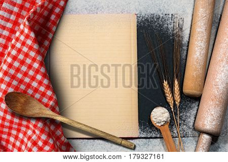 Empty recipe book with lined paper on a baking background with flour ears of wheat wooden kitchen utensils and a checkered tablecloth