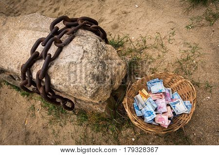 Old Rusty Chain and Basket Full of Brazilian Real Notes, Slavery Concept