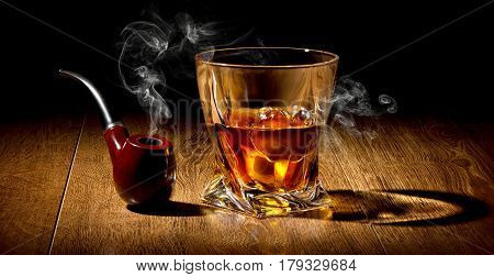 Tobacco pipe and whiskey on a wooden table