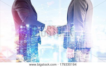 Close up of two businessmen shaking hands while standing against a night city background. Toned image. Double exposure