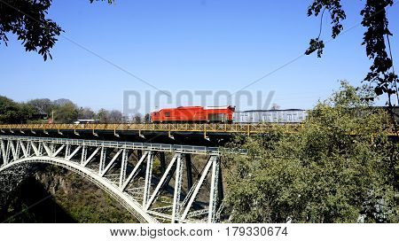Red train rides on an iron bridge and blue sky