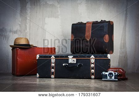 Background stack of old shabby suitcases and the camera. Concept traveler longer trips