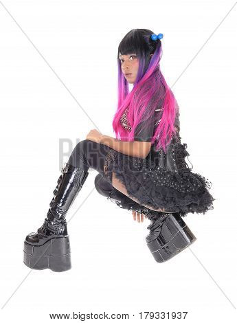 A beautiful African American steampunk woman in a black corset kneeling in a short skirt and long boots isolated for white background.