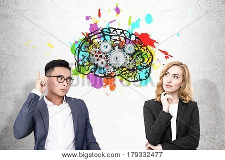 Portrait of an Asain businessman and a blond woman standing near a concrete wall with a colorful brain sketch and cogs drawn on it.