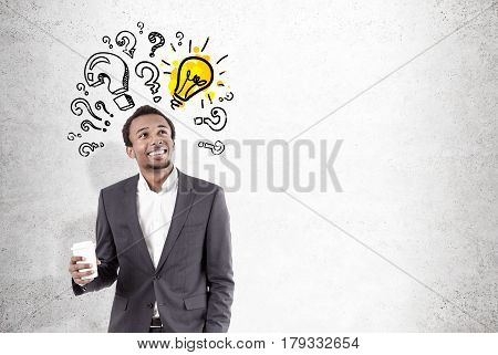 Portrait of a happy African American businessman standing with his cup of coffee near a concrete wall with question marks and a yellow light bulb drawn on it. Mock up