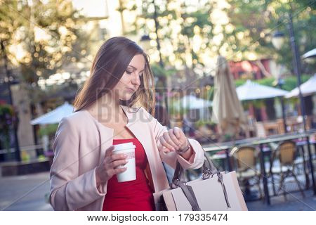Young pretty elegant woman checking time looking at her watch, hurrying down city street, holding cup of coffee.