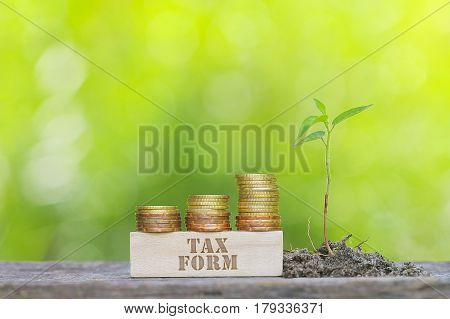 Tax Form Word Golden Coin Stacked With Wooden Bar On Shallow Dof Green Background.