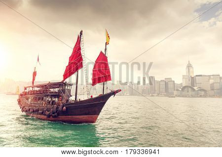 Morning sunrise over Hong Kong skyline with traditional Chinese junk crossing Victoria Harbor. HDR rendering.