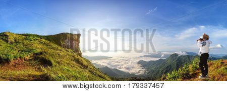 Panorama beautiful landscape nature of sunrise on peak mountain with sun cloud fog bright sky and woman tourist are taking photos in winter at Phu Chi Fa Forest Park Chiang Rai Province Thailand