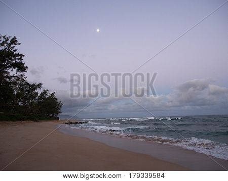 Waves roll into shore at day break with moon in the sky on the North Shore beach on Oahu Hawaii.