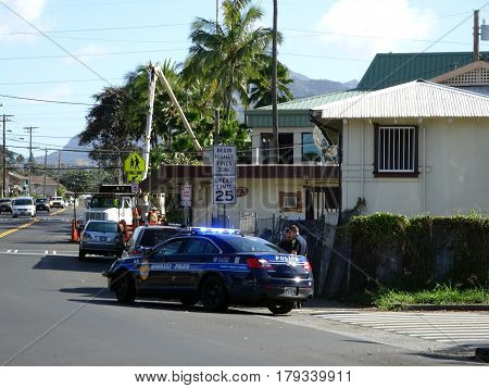 HONOLULU - FEBRUARY 7: Honolulu Police Department police officer pulls over Van on street. The HPD officer is using a white and blue cruiser with lights flashing as he talks to person outside car Hawaii February 7 2017.