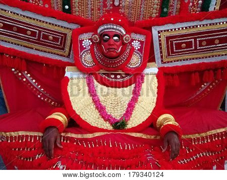 Artist of the ancient art theater Kathakali in suit and mask: bright red wide clothing garland of red flowers red mask with metal eye sockets Kerala South India.