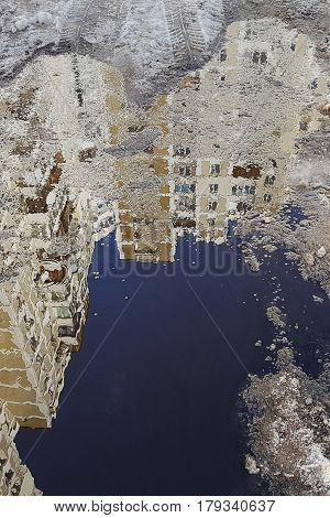 A Puddle In The Surface Of Which A Tall Building With Numerous Windows Is Reflected, A Little Snow A